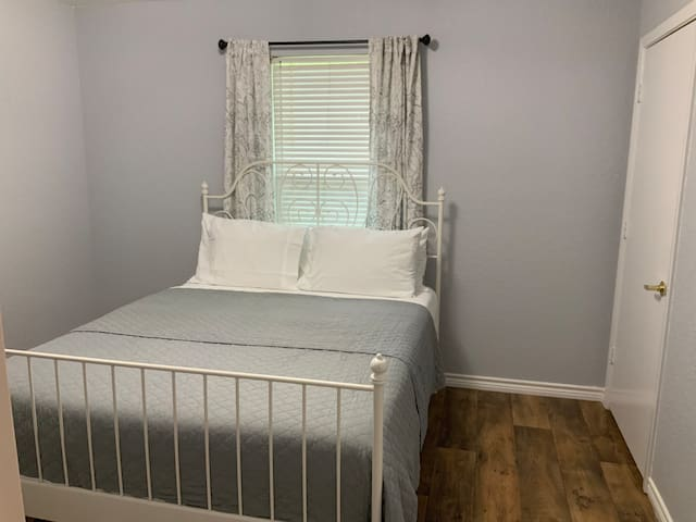 This small yet spacious master bedroom has a queen size bed.