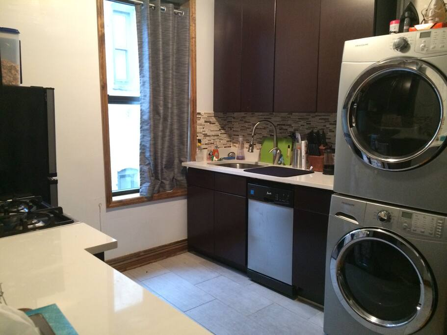 Fully furnished kitchen with washer and dryer set.
