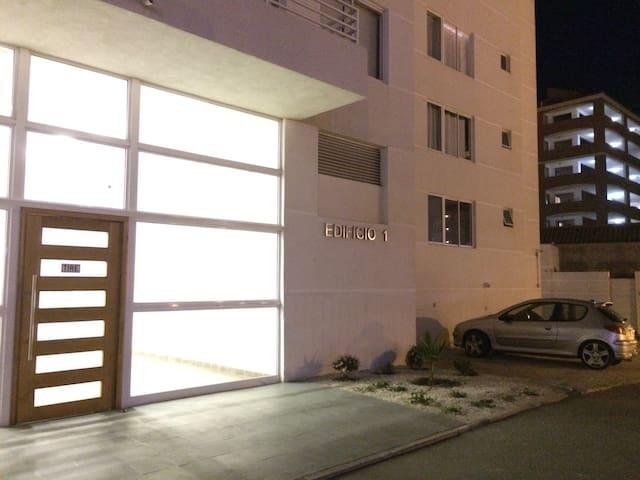 estacionamiento interior a un costado de ingreso a edificio.