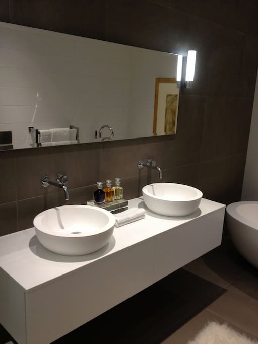 Private ensuite bathroom with dual sink and high end bath products.
