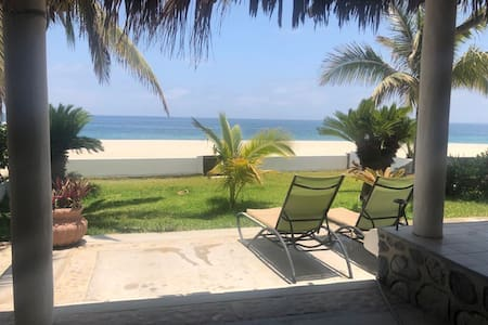 beachfront cabaña with grass lawn
