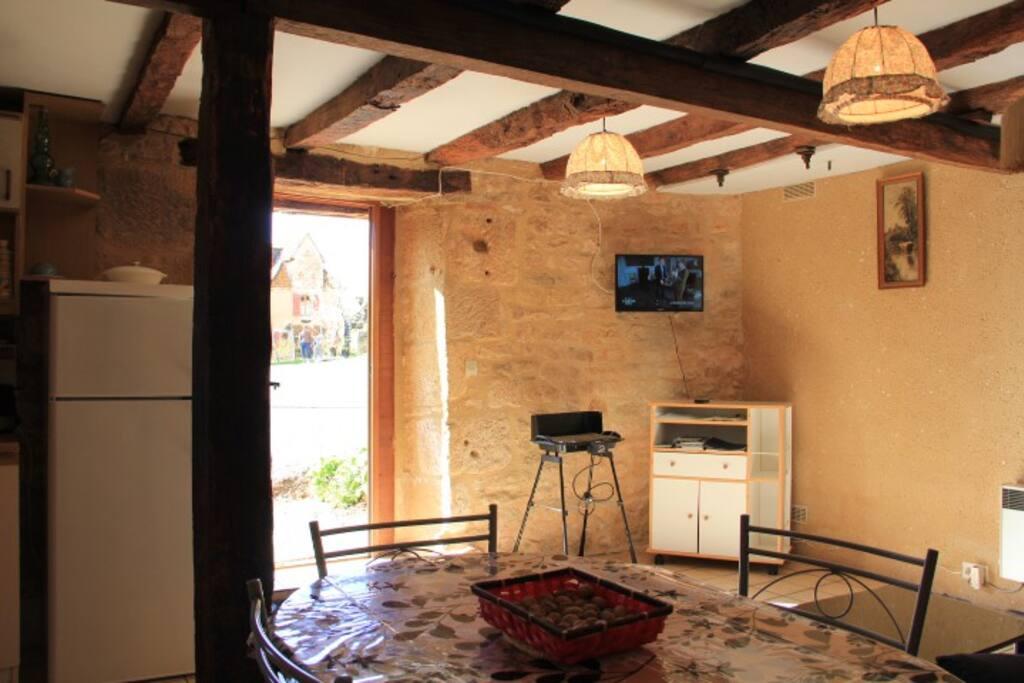 Salon ensoleillé, avec murs en pierres et poutres apparentes.