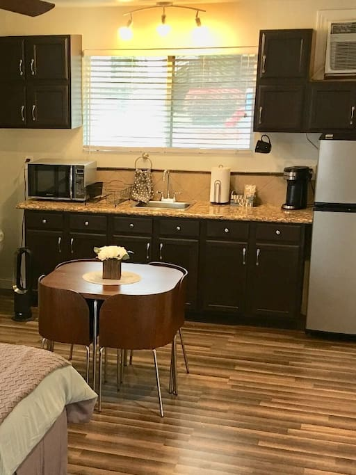 Dining table for 4. Granite kitchen countertops with stainless steel fridge, Coffee maker and coffee pods, hot plate for cooking with frying pans, dishes, utensils, and microwave.