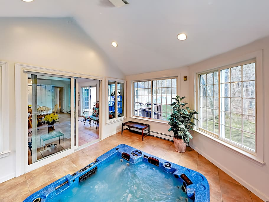 The indoor hot tub offers wall-to-wall views of the lush property.