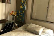 Quarto com cama de casal, TV e armário