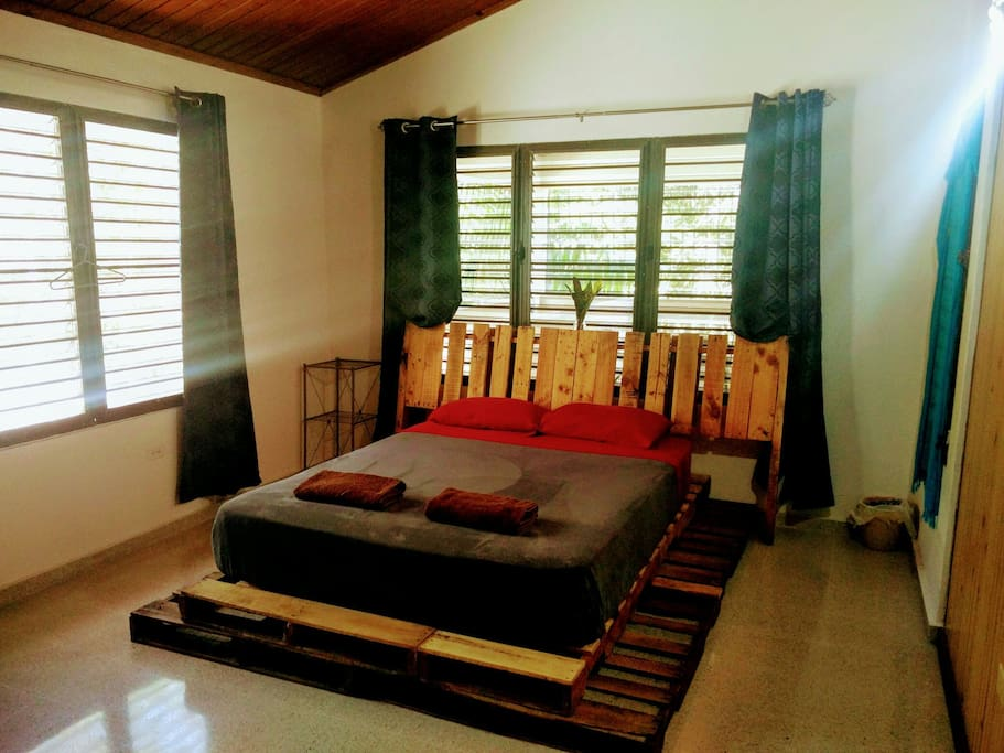 Bright room with high ceiling, queen bed and homemade bed frame with pallets
