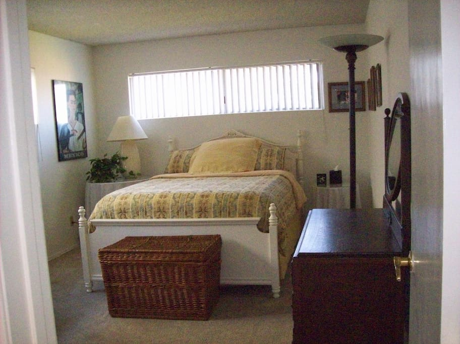 Furnished private bedroom in downstairs with desk, dresser, and closets.