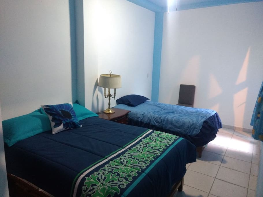 Segunda habitación con cama matrimonial e individual, con closet y ventilador. Secondary room with a queen and twin sized bed, closet and fan.