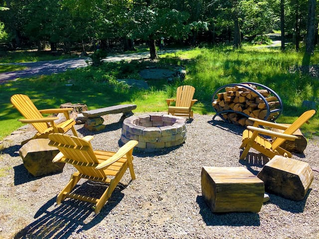 Outdoor fire pit with Adirondack chairs and stumps