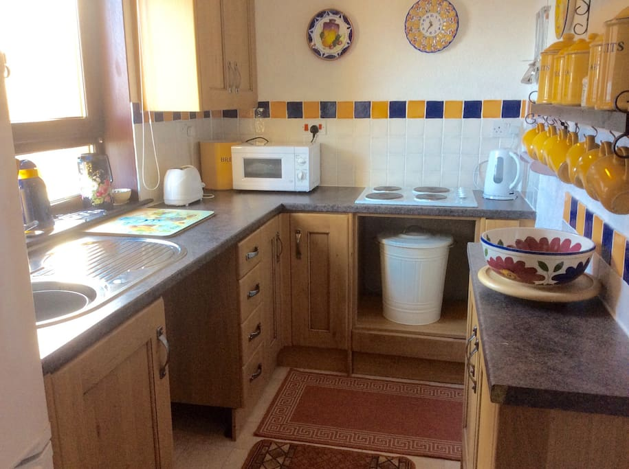 Our pretty little kitchen looks straight out to sea, it includes a fridge freezer, microwave oven, electric hob, a kettle and toaster with a good variety of pans and crockery.
