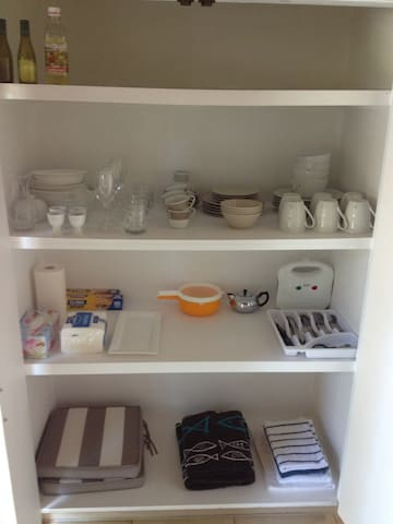 Kitchen cupboard with crockery, cutlery and utensils.