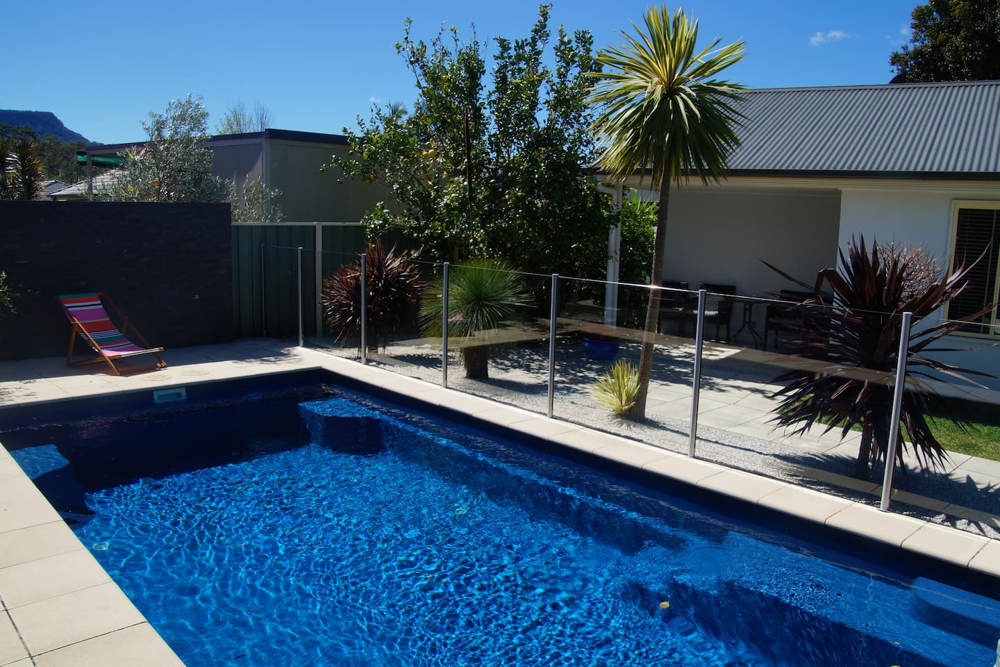 Pool with deck chairs & floats available to use.