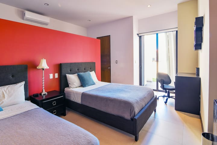 To the left we have a bedroom with two double beds that sleeps up to four people. There is a desk and private patio as well as bathroom. Large open closet space is behind the red wall outside the bathroom door.