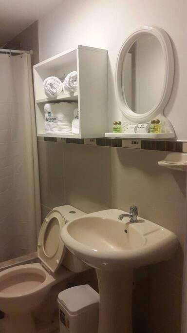 baño con accesorios de baño como toallas secamanos shampoo jabon liquido acondicionador para cabello lavadero inodoro ducha espejo estante