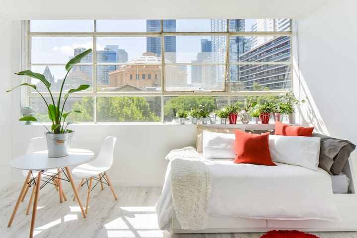 The living room is bright, filled with plants and looks out onto the State Library.