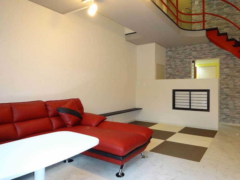 Loft style apartment with the entrance and sleeping area at upper zone, and living area and washroom downstairs.