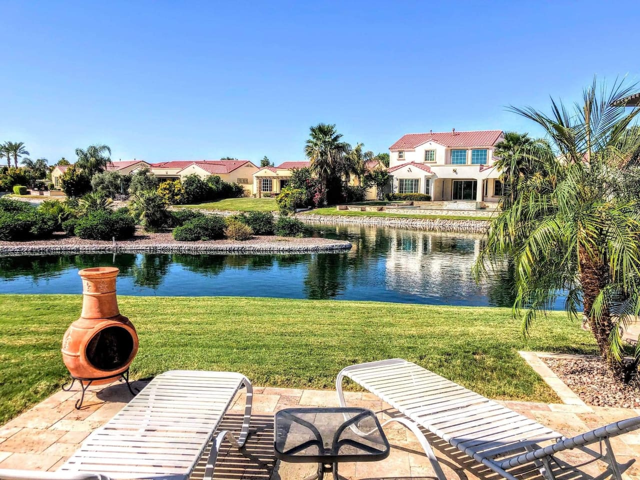 Large back yard with grass, lots of seating, fire pit, all on the water