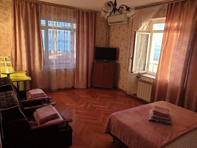 Комната. Видна двухспалка, два кресла-кровати, рабочий стол, телевизор, и кондиционер. Окно закрывается, левее телевизора выход на лоджию.