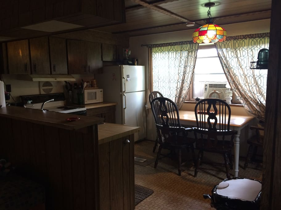 Kitchen area includes oven/ stove, full size refrigerator, microwave, coffee pot, and toaster.