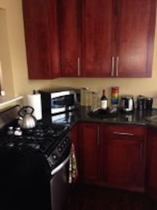 Full kitchen with beautiful cherry cabinets and granite countertops that is stocked with everything you might need to prepare a home cooked meal.