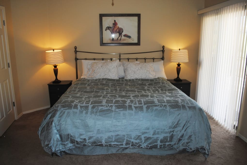 Master bedroom with exceptionally comfortable king bed with sitting area outside on the patio