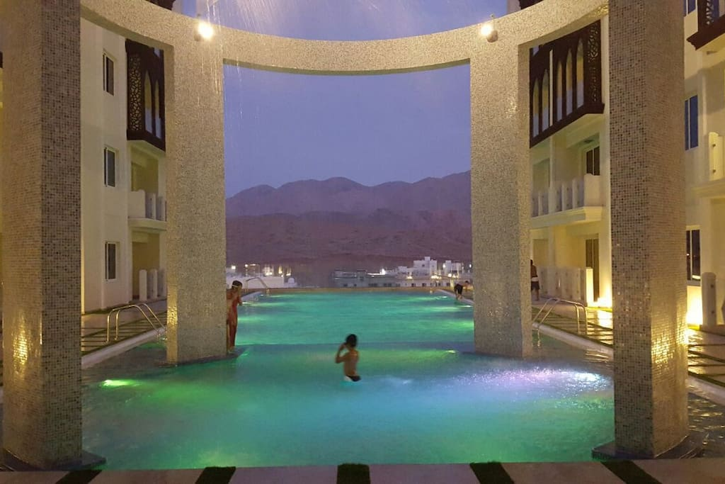 Free big swimming pool for adults and kids with changing color lightings with lovely sand dunes view