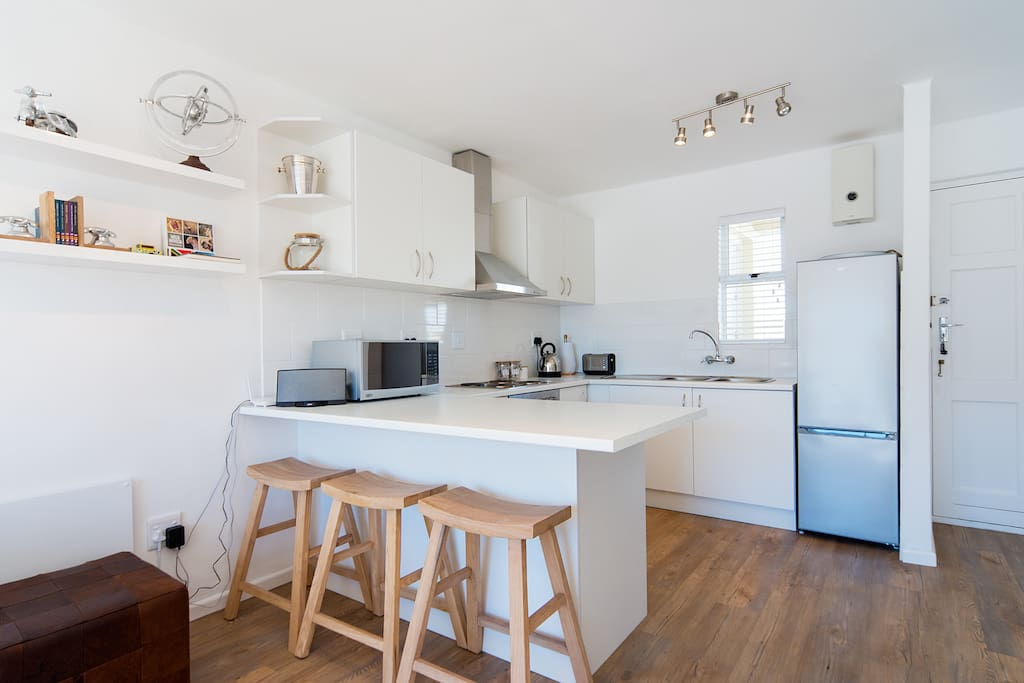 Open plan kitchen area including stove / oven, fridge / freezer, microwave, kettle and toaster.