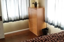 Bedroom with queen bed and a 4 drawer dresser.