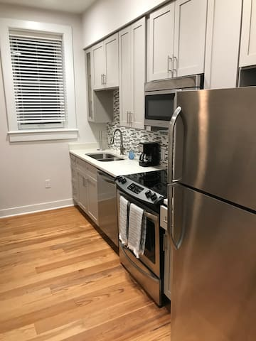 Stainless steel appliances, with tile backsplash and quartz countertops. Appliances include refrigerator, stove, microwave, coffee maker.