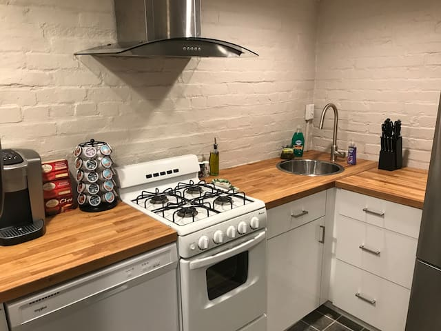 Freshly painted kitchen that includes a Keurig coffeemaker, knife block, and a newly installed range hood to meet all of your cooking needs. Pots, pans, and a microwave are also included. There is also a hopper window for great natural light.