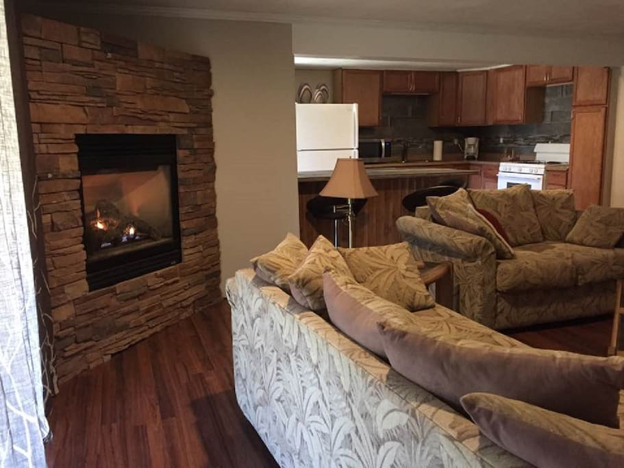 View of living, fireplace and kitchen area.