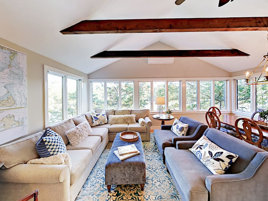 Seating for 9 in the living area with vaulted ceilings, exposed wood beams, and lots of natural light.