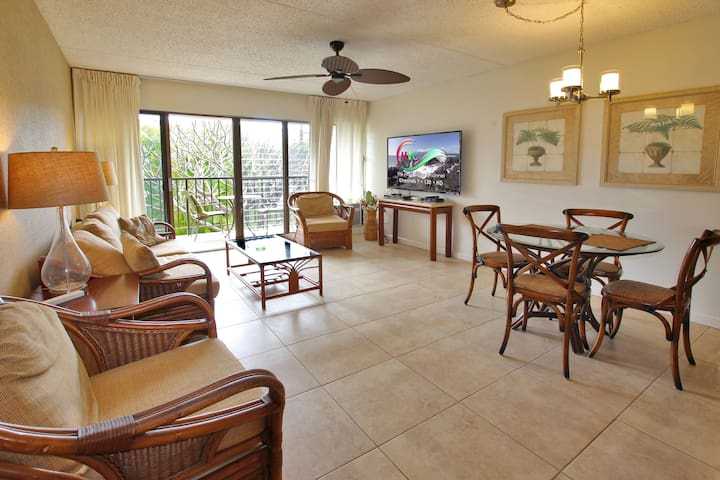 Bright and sunny living room with air conditioner opens up to private balcony lanai with garden view