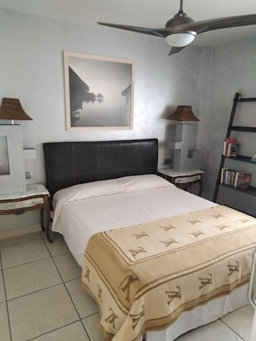Habitación principal con cama de matrimonio, ventilador de techo que funciona con un mando, un armario y mesitas de noche