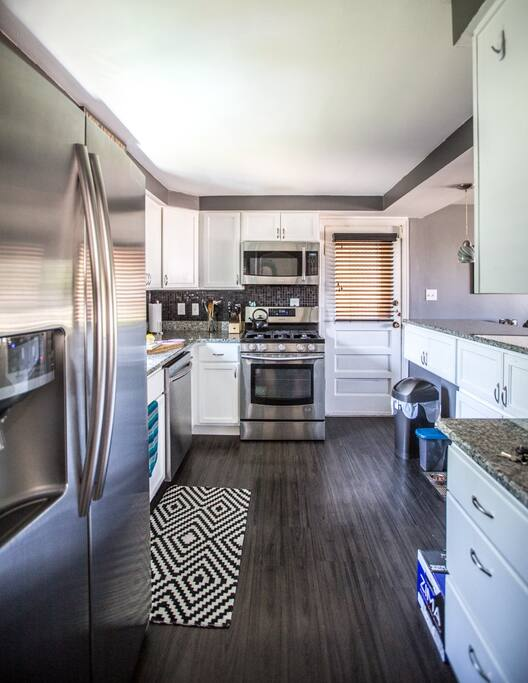 Kitchen features a gas top stove, dishwasher + all stainless steel appliances.