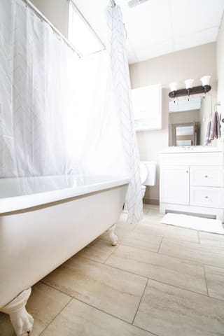 Charming claw foot tub with shower.