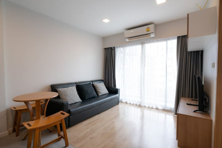 Living room; separated from bedroom by wooden door. Small tea table, sofa, television air conditioner and small balcony are provided in this room.