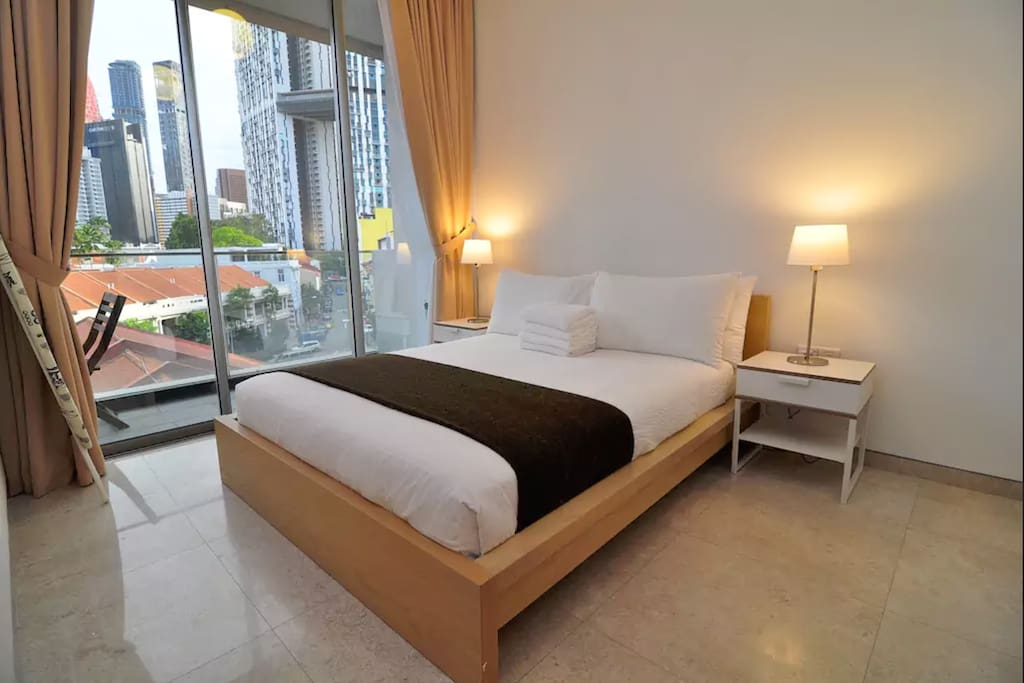 Master bedroom with queen bed, ensuite bathroom, and large balcony.