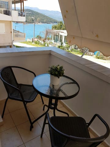 Relaxing balcony with table and chairs, sun blinds with view of the Ionian sea and Corfu island