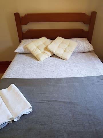 Cama de Casal em madeira no quarto.