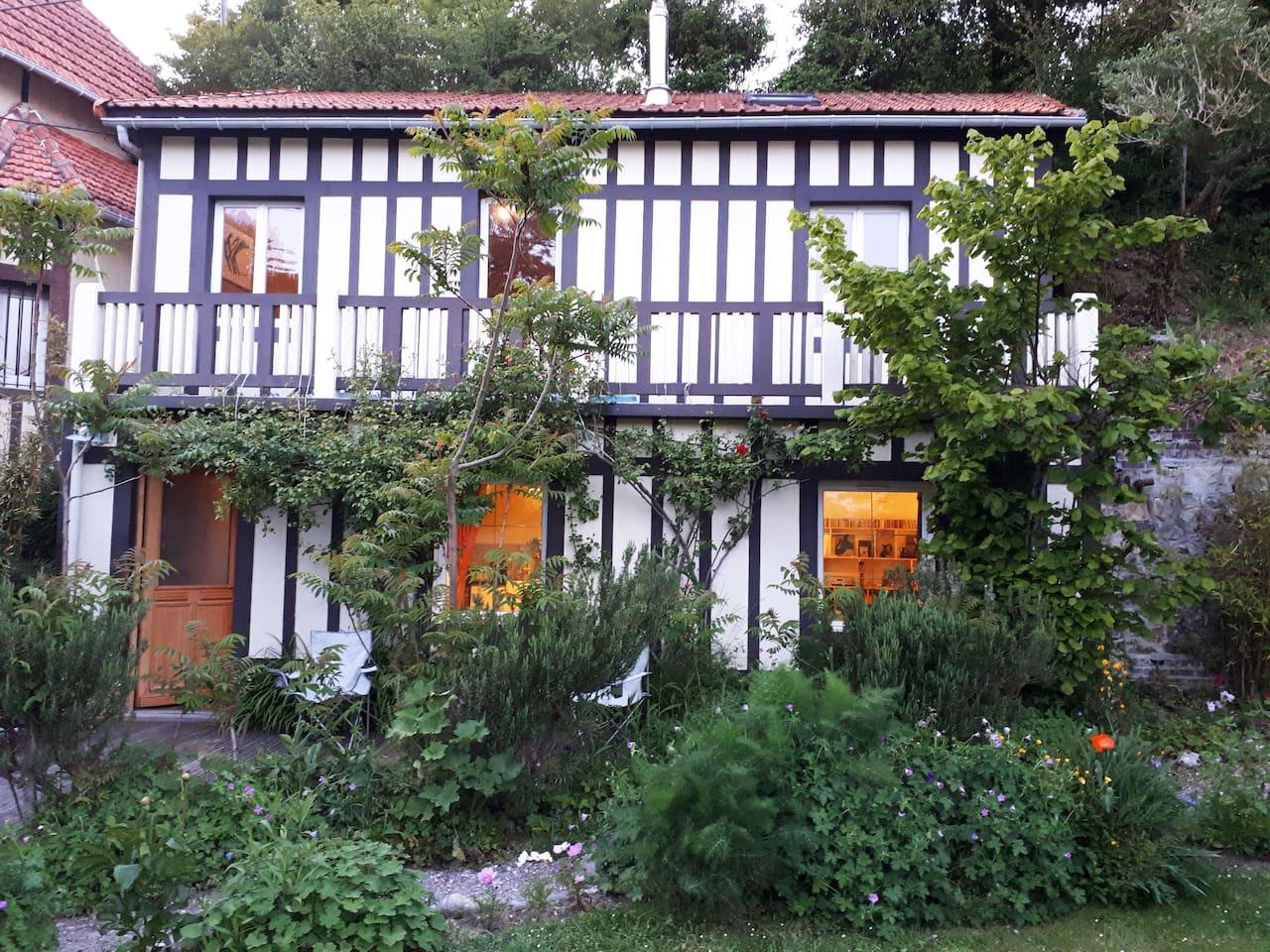 Façade de la maison sur deux niveaux avec terrasse arborée.