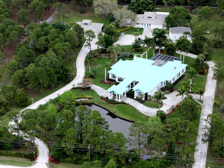 Aerial shot of the 5400 sf Tropical Retreat Airbnb rental home. (The Estate Home is highlighted by the soft sea green colored metal roof).