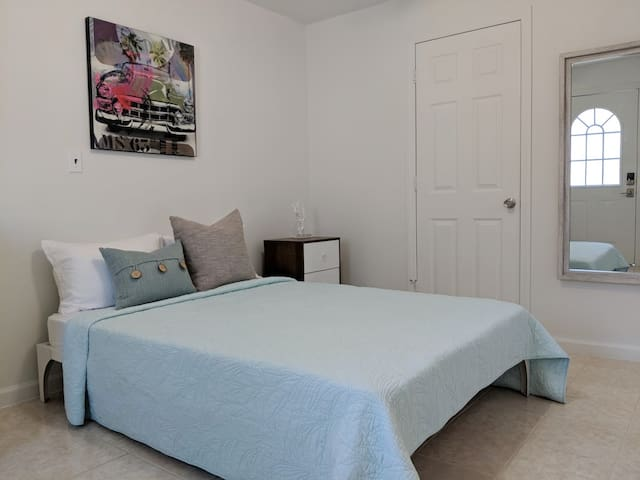 Comfortable Full Size Bed with an USB charging socket on wall between the bed and end-table.