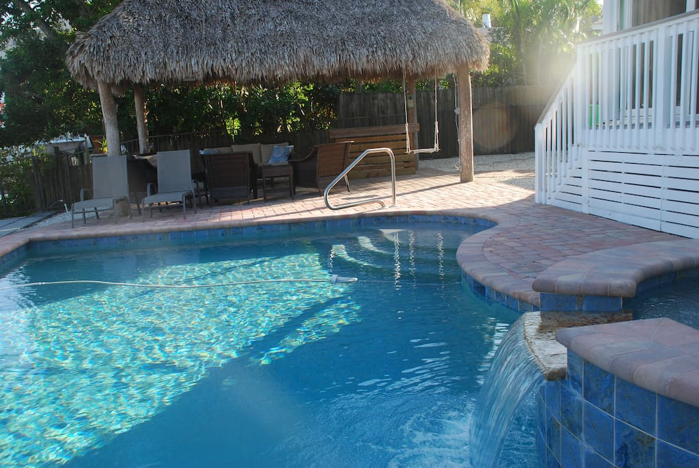 Beautiful pool and hot tub along side tiki hut and canal.