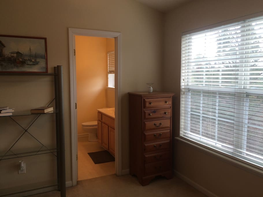 Looking into private bathroom from bedroom