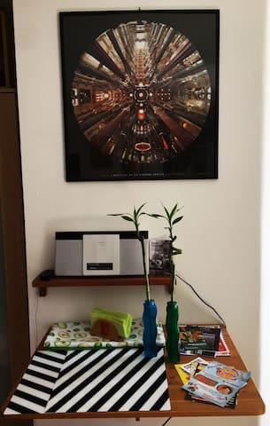 la radio con il telecomando, il quadro della Sagrada Familia, il tavolo a ribalta con depliant sugli eventi a Genova e le pizzerie in zona...
