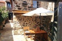 Patio con sol, mesa, sillas y sombrilla