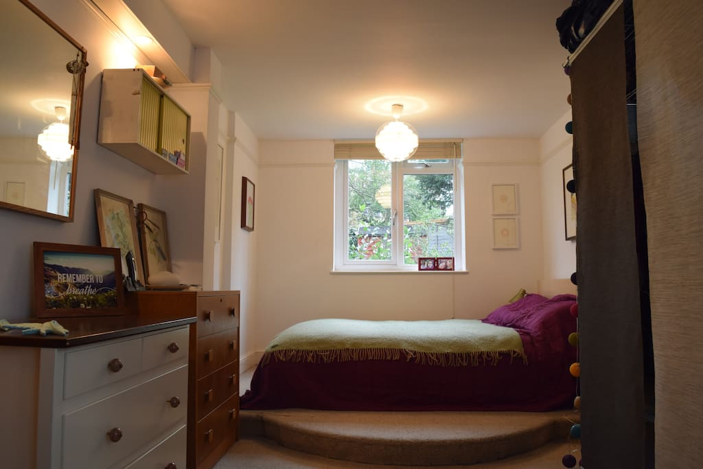 This is our large bedroom with a view of the back garden outside.