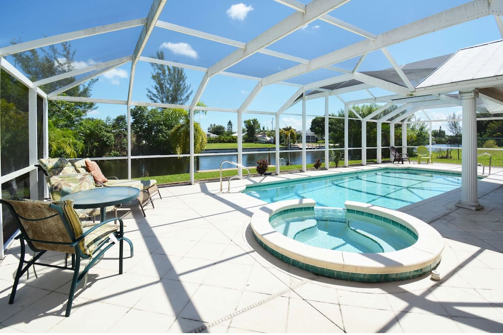 Screen-enclosed pool and spa overlook the canal.