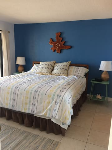 The bedroom has a king sized pillowtop bed, funky beach decor and a bluetooth alarm clock that allows you to play music direct from your devices to listen to throughout the house.